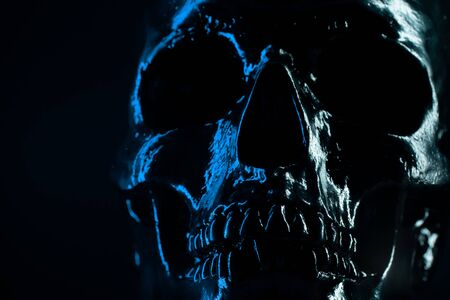 Human blue skull on dark background. Concept of fear, death and horror, Halloween celebration. Spooky and sinister.