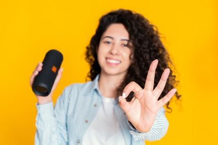 Modern girl with wireless portable speaker showing ok sign. Young beautiful woman with curly hairstyle enjoying at yellow background Banco de Imagens