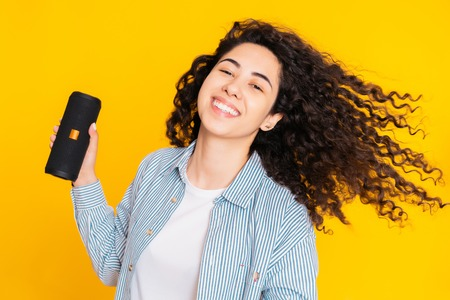 Modern trendy girl listening to music by wireless portable speaker. Young beautiful woman with curly hairstyle enjoying and dancing at yellow background. Female moves to the rhythm of music