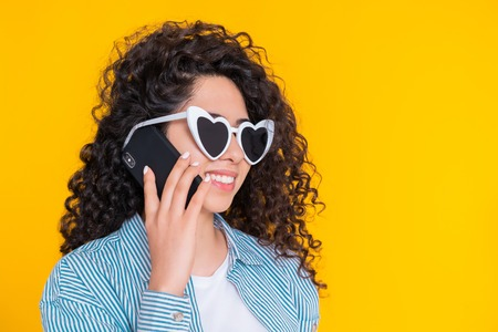 Young female smiling and talking on mobile phone over yellow background. Beautiful mixed race girl holding and using smart phone. Woman with technology. Banco de Imagens