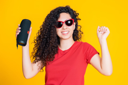 Young beautiful woman with curly hairstyle enjoying and dancing at yellow background. Modern trendy girl listening to music by wireless portable speaker.