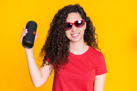Young beautiful woman with curly hairstyle enjoying and dancing at yellow background. Modern trendy girl listening to music by wireless portable speaker Banco de Imagens
