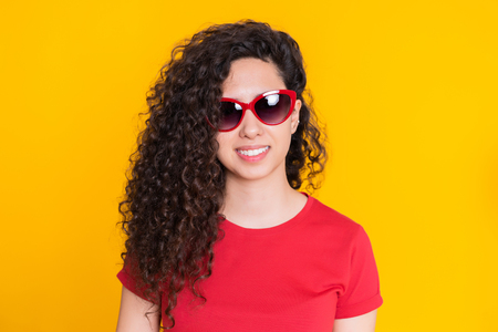 Pretty girl with curly hairstyle on yellow background. Beautiful portrait of woman in red t-shirt smiling and looking at camera. Latin or hispanic race young model