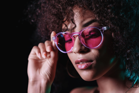 Alluring unusual girl with curly afro hair corrects her glasses. Sexy woman with perfect makeup looking at camera and smiling. Glamour, fashion concept.