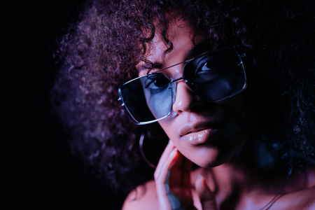 Portrait of young seductive african american girl in neon light at black background. Tempting woman with perfect makeup looking at camera and smiling. Glamour, fashion concept