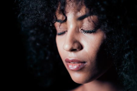 Portrait of afro girl. Tempting woman with perfect makeup and curly hairstyle smiling. Glamour, fashion, model, healthy skin concept. Copy space.