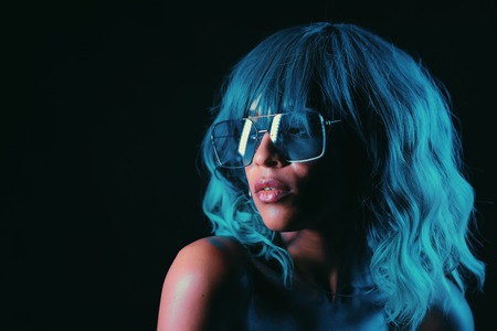 Portrait of alluring blue haired mixed race girl in neon light. Fashion, glamour, model concept. Seductive woman with make-up and transparent glasses posing in dark room at night Banco de Imagens