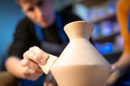 Working process of mans work at potters wheel in art studio. Unknown craftsman creates jug. Focus on hands only. Small business, talent, invention, inspiration concept