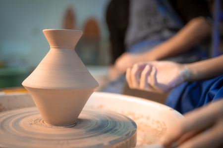 Working process of mans work at potters wheel in art studio. Unknown craftsman creates jug. Focus on hands only. Small business, talent, invention, inspiration concept. Stok Fotoğraf