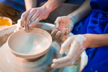Traditional pottery making, man teacher shows the basics of pottery in art studio. Artist operates hands, which gently creating correctly shaped jug handmade from clay Banco de Imagens