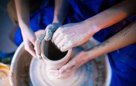 Hands of potter and his female student. Man and woman working together, creating clay product on potter wheel. Traditional pottery making, teacher shows basics of pottery in art studio.