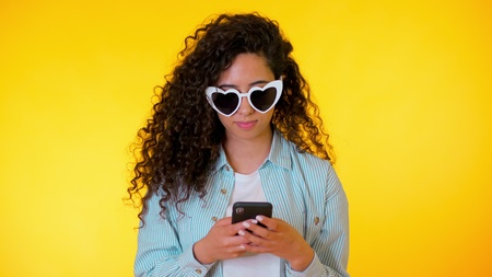 Young female smiling and using mobile phone over yellow background. Beautiful mixed race girl holding and texting with smart phone. Woman with technology