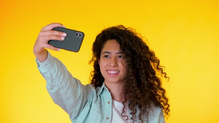 Beautiful woman with curly hair holding and using smart phone to film herself in yellow studio. Female using technology networking on holiday, lifestyle Banco de Imagens