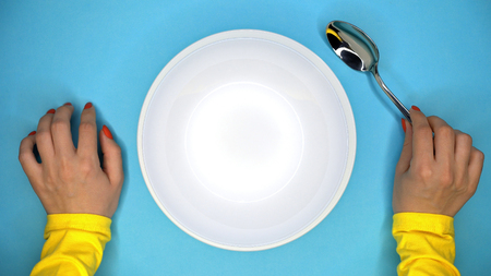 Hands of young woman with spoon. Lady sitting in restaurant and waiting for order. Empty white plate on blue background Banco de Imagens