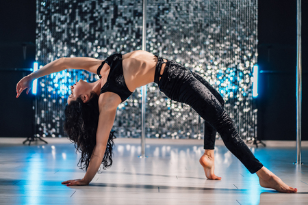 Woman doing tricks, practicing in studio with pylon. Young stripper in black dances sexually with pole in club. Poledance on shining wall background