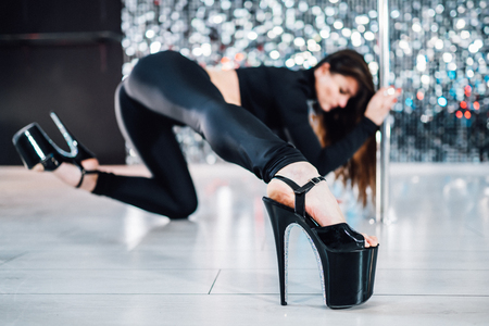Sexy woman in high heels dancing with pylon in art-studio. Poledance on shining wall background. Stok Fotoğraf
