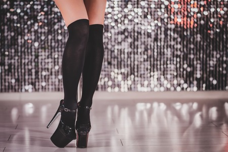 Close-up legs of unrecognizable woman. Young stripper in black stockings in night mens club. Poledance on shining wall background Stok Fotoğraf