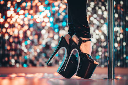 Legs in high sexy shoes near pylone. Striptease dancer moving on stage in strip night club. Pole dancing background.