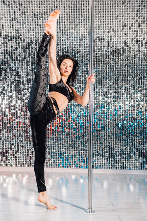 Woman doing tricks with pylon. Young stripper in black dances sexually with pole in studio or club. Poledance on shining wall background Stok Fotoğraf