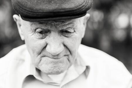 Old man portrait. Grandfather in hat. Portrait: aged, elderly, loneliness, senior with lot of wrinkles on face. Close-up of a pensive man sitting alone. Black and white Stok Fotoğraf