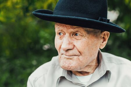 Old senior portrait. Grandparent in hat. 90 plus year. Portrait: aged, elderly, loneliness, man with lot of wrinkles on face. Close-up of a pensive old man sitting alone outdoors.