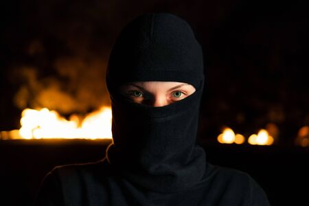 Portrait of female protesting activist in black balaclava against burning barricades at night. Concept of strikes, political conflicts and confrontation