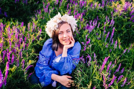 Young pretty woman with flower wreath sitting in purple field. Portrait of girl in blue clothing.