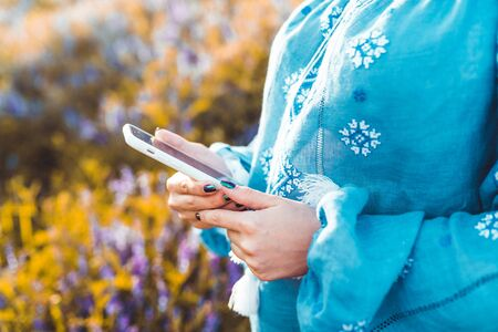 Hands of woman using smartphone in flowers field. Technology, surfing internet, communications concept.