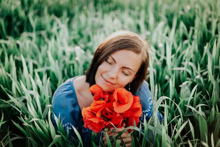Young pretty woman with poppies bouquet in green field. Beautiful background. Smiling girl. Nature, freedom, flowers concept. Stok Fotoğraf