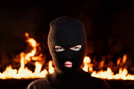 Portrait of young woman in black balaclava against backdrop of a blazing night fire. Concept of mass rallies and riots Stok Fotoğraf