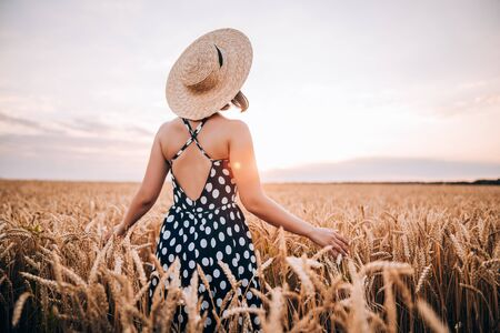 Unrecognizable woman in retro style dress and hat posing in wheat golden field. Travel, harvest, nature, old fashion concept. 版權商用圖片