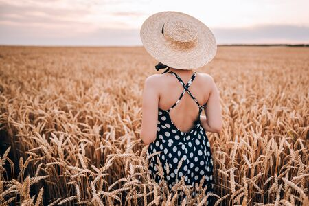 Unrecognizable woman in retro style dress and hat posing in wheat golden field. Travel, harvest, nature, old fashion concept. Stok Fotoğraf