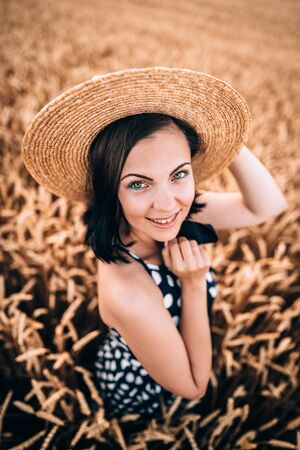 Portrait of woman in retro style dress and hat posing in wheat golden field. Travel, harvest, nature, old fashion concept. Stok Fotoğraf