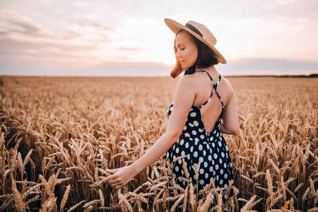 Woman in retro style dress and hat posing in wheat golden field. Travel, harvest, nature, old fashion concept.