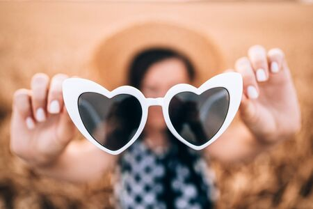 Close-up of white heart-shaped sunglasses. Woman holding glasses in hands. Fashion retro concept.