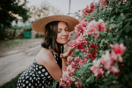 Elegant young woman in retro styled dress and hat posing on roses background. Beautiful girl in old european countryside.