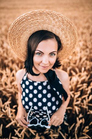 Portrait of woman in retro style dress and hat posing in wheat golden field. Travel, harvest, nature, old fashion concept. 免版税图像