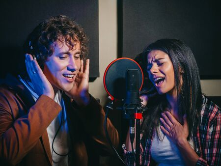 Two young singers performing their song in record studio. Professional musician duet recording new album CD. Beautiful couple working together.