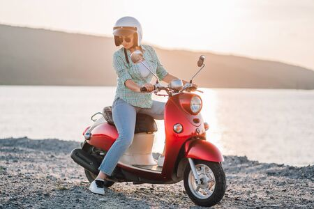 Cute girls portrait. Woman in helmet and sunglasses sitting on red retro motor bicycle at sunset river background. Cinematic vintage toned. Copy space