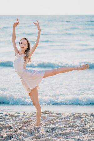 Young pretty ballerina in beige dress dancing ballet on sea or ocean sandy beach in morning light. Concept of stretching, art, nature beauty