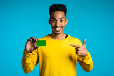 Young handsome african american man holding in hand green card. Credit or playing card, finance, vacation, visa concept. Foto de archivo