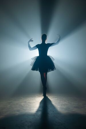 Solo performance by ballerina in tutu dress against backdrop of luminous neon spotlight in theater. Silhouette of woman in pointe shoes dancing classical movements.