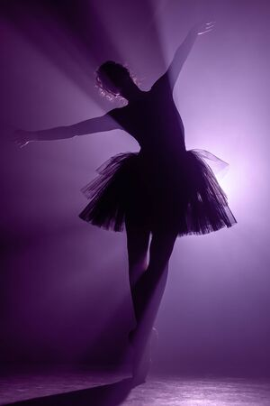 Silhouette of impressive girl dancing ballet in tutu on stage in front of spotlight with colored violet neon light. Copy space. Volumetric painting, smoke scene.