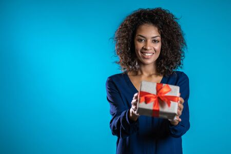 Mixed race woman gives gift and hands it to the camera. She is happy, smiling. Girl on blue background. Positive holiday picture. Copy space