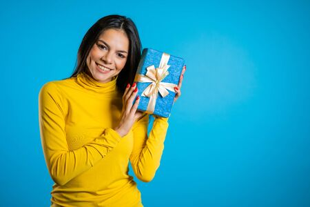 Beautiful spanish woman received gift box with bow. She is happy and flattered by attention. Girl on blue background.