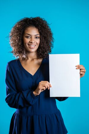 African american woman holding white a4 paper poster. Copy space. Smiling pretty girl with curly hairstyle on blue background.