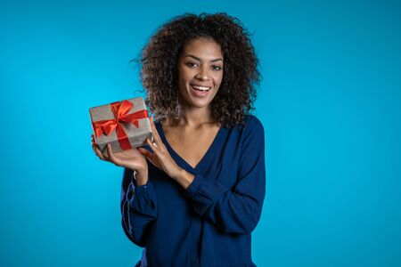Pretty woman received gift box and interested in whats inside. She is happy and flattered by attention. Girl on blue background. Studio picture.
