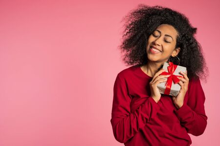 Beautiful african american woman received gift box with bow. She is happy and flattered by attention. Girl on studio background.