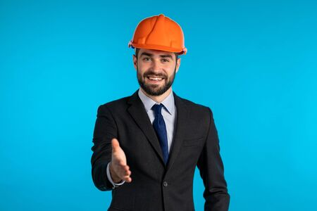 Young engineer businessman in construction helmet holds out his hand for greeting, handshake. Man with beard in corporative suit over blue background.