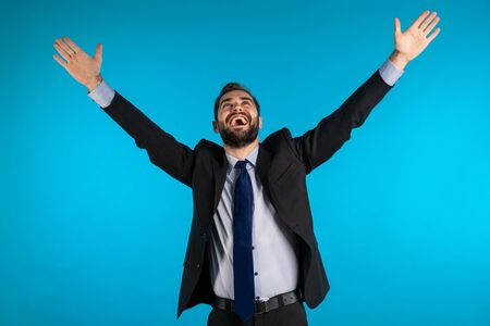 Yes winner gesture. Amazed european businessman with beard shocked, saying yeah. Handsome guy with stylish hairdo and beard surprised to camera over blue background. Stok Fotoğraf